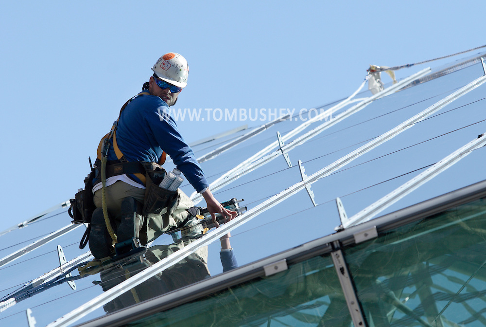 New Paltz, New York - A man works on glass panels on the roof of the addition to the Student Union Building at the SUNY New Paltz.  The building is clad in 315 panels of energy-efficient glass. March 22, 2010.