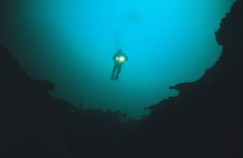 A diver glides above a hole in the deck on the wreck of D/S Nesodtangen. Location: Norway