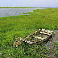 A washed up row boat looks lonely  and serves as a harbinger of days gone by as it sits in the marshland on Scow Creek in Hempstead Bay, July 14, 2014.   © Audrey C. Tiernan