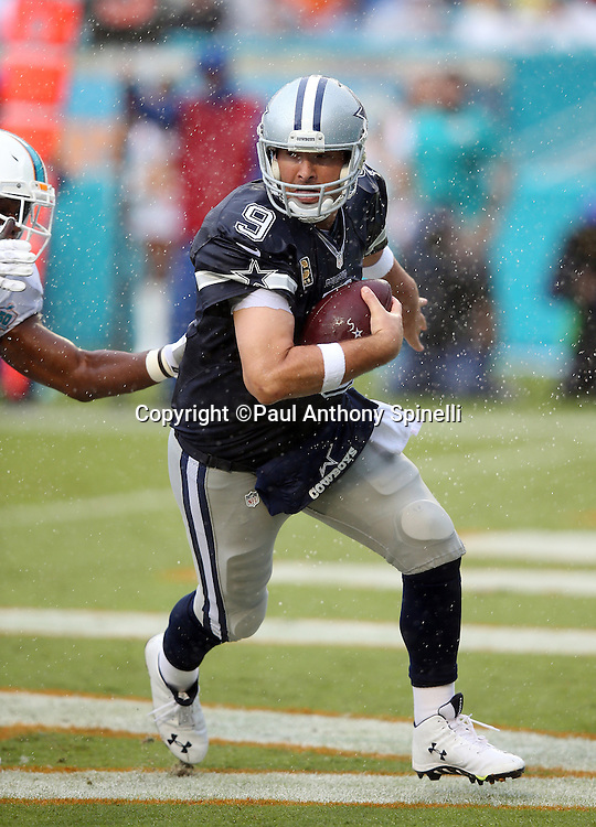Dallas Cowboys quarterback Tony Romo (9) scrambles in his own end zone while avoiding a sack and a potential safety by Miami Dolphins linebacker Neville Hewitt (46) on a first quarter play in which he throws a completed pass with his left hand during the 2015 week 11 regular season NFL football game against the Miami Dolphins on Sunday, Nov. 22, 2015 in Miami Gardens, Fla. The Cowboys won the game 24-14. (©Paul Anthony Spinelli)