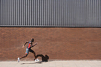Man running past brick wall