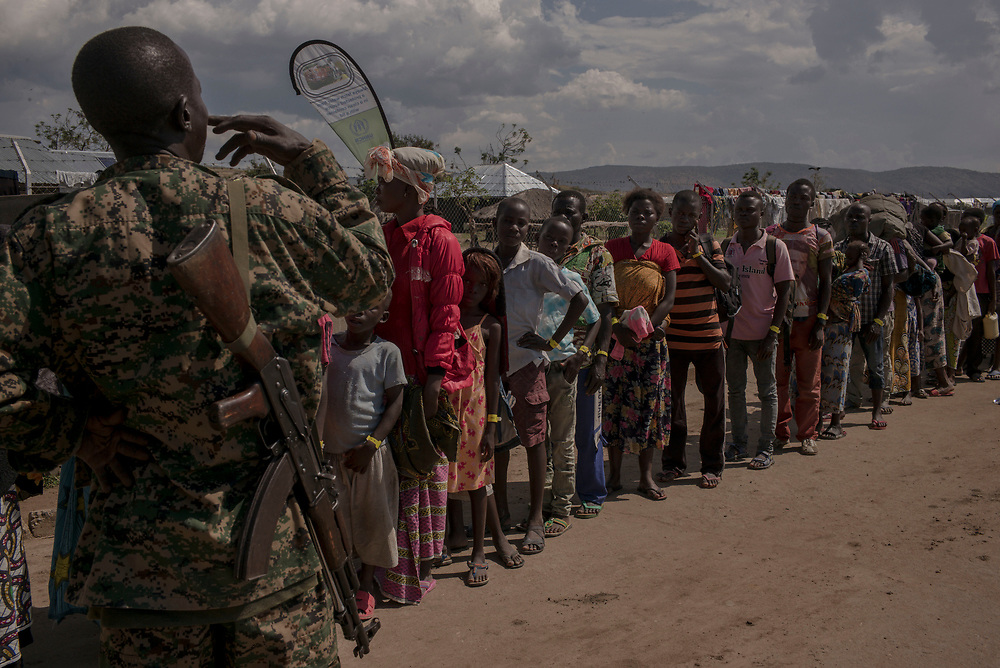 SEBAGORO, UGANDA - MARCH 22: Congolese refugees wait in line for a bus bound for Kyangwali refugee settlement camp after landing in Sebagoro, Uganda on March 22, 2018. Violence in Ituri Province in northeastern Democratic Republic of Congo has displaced more than 100,000 people including approximately 40,000 refugees who have fled to Uganda. (Photo by Andrew Renneisen for The Washington Post)