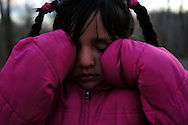 A young girl rubs her eyes after tripping on the asphalt in the Southwood mobile home park. She is from one of the community's many Mexican immigrant families. (photo by Shannon Jensen)