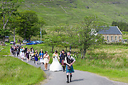 Traditional Highland Scottish wedding with piper leading procession of bride and groom and wedding guests from Clachan Church in to the wedding reception in Applecross, Highlands of Scotland