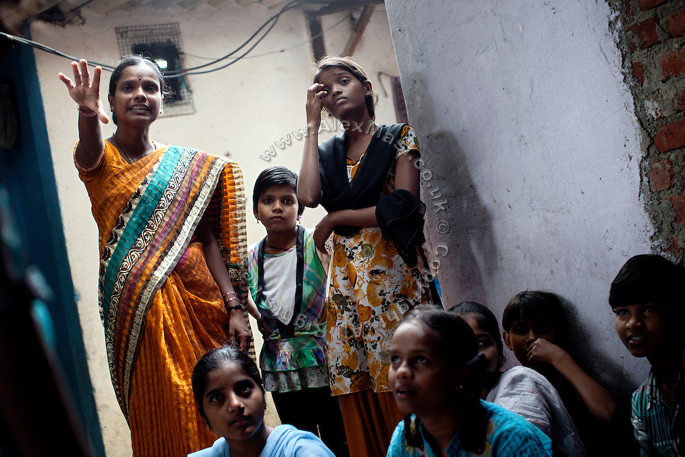 Anita Suresh Kasbe,  41, (left) the Unicef community facilitator is teaching to the girls - and others - attending the Unicef-run 'Deepshikha Prerika' project inside the Milind Nagar Pipeline Area, an urban slum on the outskirts of Mumbai, Maharashtra, India.