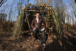 Kevin Langan with his hut on the wasteground near Ibrox. He has set himself the challenge of building 100 small huts on any land where they can be made from the natural resources. www.100wildhuts.com