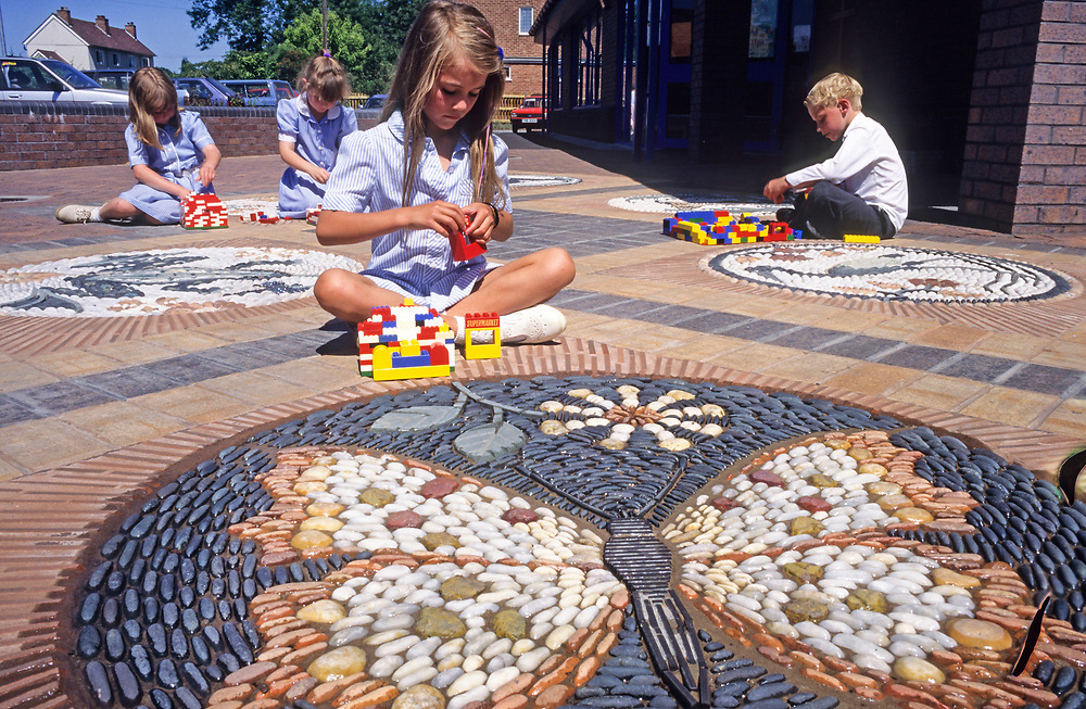Children in the playground building with lego.