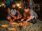 26 DECEMBER 2014 - PATONG, PHUKET, THAILAND: Tourists light candles during the memorial for the victims of the 2004 tsunami on Patong Beach in Patong, Phuket. Hundreds of people died in Patong and nearly 5400 people died on Thailand's Andaman during the 2004 Indian Ocean Tsunami that was spawned by an undersea earthquake off the Indonesian coast on Dec 26, 2004. In Thailand, many of the dead were tourists from Europe. More than 250,000 people were killed throughout the region, from Thailand to Kenya. There are memorial services across the Thai Andaman coast this weekend.    PHOTO BY JACK KURTZ