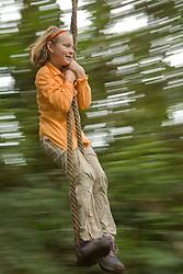 Girl (age 7) on rope swing in cloudforest, Sachatamia Lodge, Mindo, Pichincha province, Ecuador, South America.  PR, MR