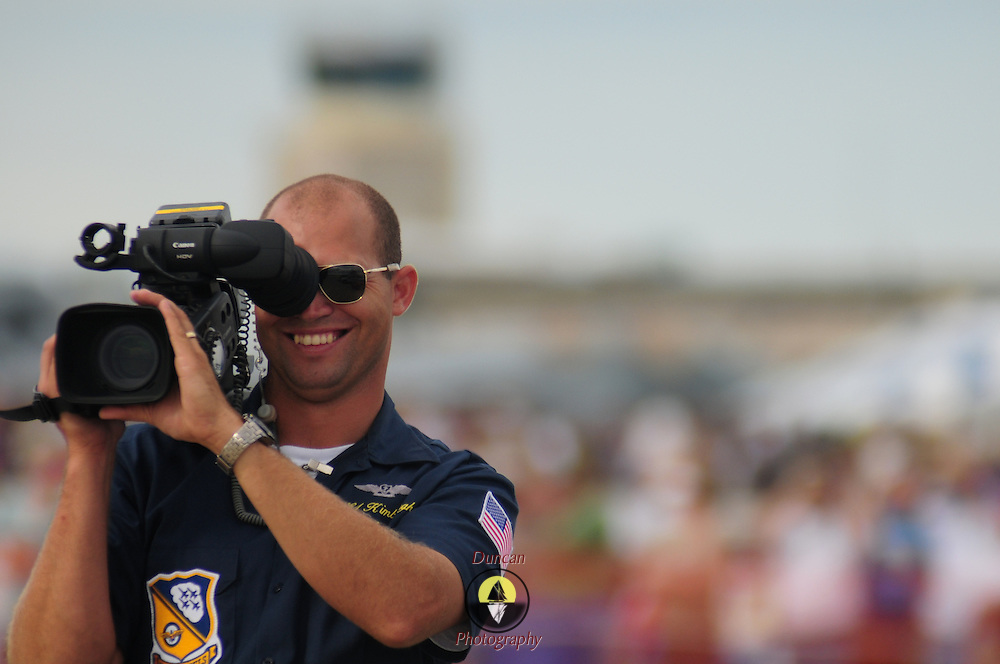 September 7, 2008 -- NAS BRUNSWICK, Maine. The Blue Angels videographer smiles for the camera as he captures the action at the The Great State of Maine Airshow on Sunday afternoon. The airshow visited Naval Air Station Brunswick for the last time this weekend, bringing The U.S. Navy Blue Angels, The U.S. Army Golden Knights and a wide variety of static displays and interactive exhibits. The show drew over 150,000 people over three days with no mishaps among the performers and no emergencies among the attendees. .Because NAS Brunswick is scheduled to be closed in 2011 by the Base Realignment Commission, there will not be another Navy-sponsored airshow at this location. Yet, the Local Redevelopment Authority, responsible for managing the property after the departure of the Navy,  has included an airshow on a list of possible future uses for the property.  U.S. Navy Photo by Mass Communication Specialist 1st Class Roger S. Duncan (RELEASED)