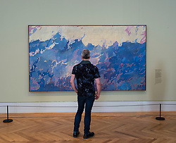 Man looking at painting Aspiration by Augustus Vincent Tack at exhibition of American art , From Hopper to Rothko at the Barberini Museum in Potsdam , Germany . Editorial Use Only
