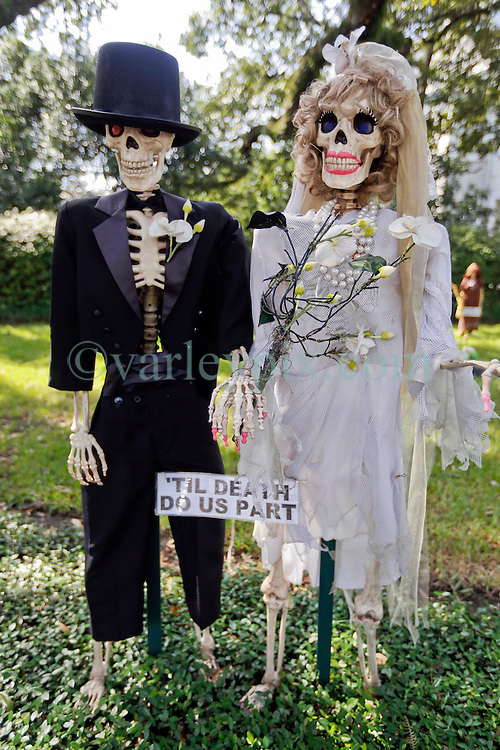 30 October 2015. New Orleans, Louisiana.<br /> The Skeleton Krewe mansion on St Charles Avenue at the corner of State Street draws crowds with its satirically spooky Halloween decorations. Til Death do us Part - spooky married skeletons.<br /> Photo©; Charlie Varley/varleypix.com