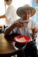 A coffee farmer has a roll and coffee for breakfast at a bakery in .Salento, Colombia