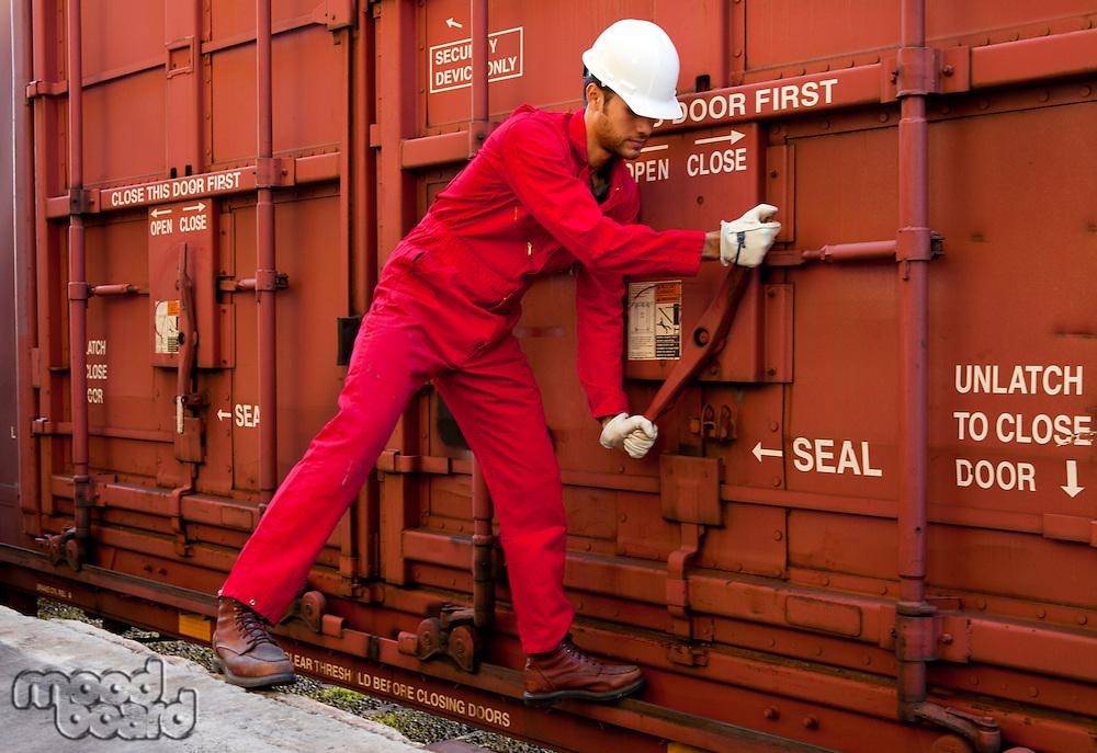 Hispanic worker opening industrial railway carriage