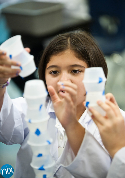 Fifth-graders Jessica Higgins, left, and Gabrielle Carbello build a tower out of plastic cups during a STEM (Science Technology Engineering and Math) class at Coltrane-Webb Elementary School Wednesday morning. (Photo by James Nix)