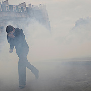 A young demonstrator blinded by overwhelming teargas is running away from Darcy Square. Dijon, France - October 15th 2010.
