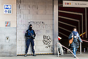 Brussels 23 March 2016.Police officers guard the metro entrance of De Brouckere. a woman leaves the metro