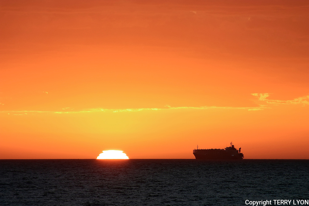 A ship heading into Fremantle Port past Cottesloe with the evening sun set