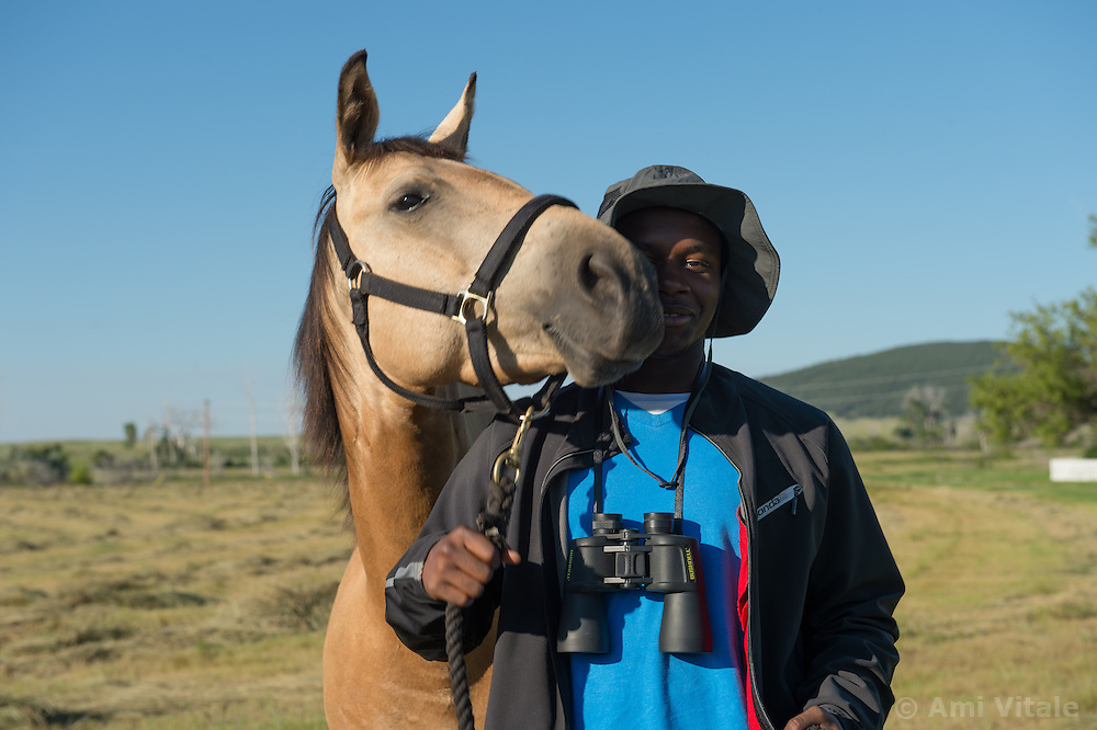 TNC LEAF volunteer Dujuan Hinton pets a horse named Dakota in Eastern Montana  at the Matador ranch &quot;grass bank&quot;. The &ldquo;grass bank&quot; is an innovative way to leverage conservation gains, in which ranchers can graze their cattle at discounted rates on Conservancy land in exchange for improving conservation practices on their own &ldquo;home&rdquo; ranches. In 2002, the <br /> Conservancy began leasing parts of the ranch to neighboring ranchers who were suffering from  severe drought, offering the Matador&rsquo;s grass to neighboring ranches in exchange for their  participation in conservation efforts. The grassbank has helped keep ranchers from plowing up native grassland to farm it; helped remove obstacles to pronghorn antelope migration; improved habitat for the Greater Sage-Grouse and reduced the risk of Sage-Grouse colliding with fences; preserved prairie dog towns and prevented the spread of noxious weeds. (Photo By Ami Vitale)
