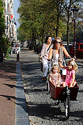 A woman cycles along Prinsengracht with her two daughters in a box on the front of the bike, Amsterdam
