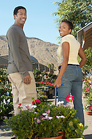 Couple pulling potted plants on cart at nursery