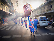 30 OCTOBER 2014 - BANGKOK, THAILAND: Chinese dragon dancers perform on Bamrung Muang Street during the parade marking the start of the annual temple fair at Wat Saket. Wat Saket is on a man-made hill in the historic section of Bangkok. The temple has golden spire that is 260 feet high which was the highest point in Bangkok for more than 100 years. The temple construction began in the 1800s in the reign of King Rama III and was completed in the reign of King Rama IV. The annual temple fair is held on the 12th lunar month, for nine days around the November full moon. During the fair a red cloth (reminiscent of a monk's robe) is placed around the Golden Mount while the temple grounds hosts Thai traditional theatre, food stalls and traditional shows.   PHOTO BY JACK KURTZ
