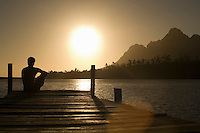 Man sitting on dock by lake back view.