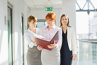 Businesswomen discussing over documents at office hallway