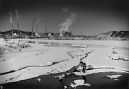 Man clears blockage where unfrozen stream, warmed by polluted factory efflent has warmed the water, enters into the Mudan River in front of a massive industrial complex, outside Mudanjiang, Heilongjiang, China.