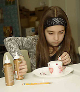 Julie Slyby, 10, who attends Ridgeville Christian School adds art and decorations to a candle at the American Girl Tea Party, Saturday, January 27, 2007 in Waynesville's Mary L. Cook Library.