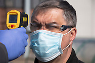 A member of staff at the Vauxhall car factory photographed having his temperature read during preparedness tests and redesign ahead of re-opening following the COVID-19 outbreak. Located in Ellesmere Port, Wirral, the factory opened in 1962 and currently employs around 1100 workers. It ceased production on 17 March 2020 and will only resume work upon the advice of the UK Government, which will involve stringent physical distancing measures being in place across the site.