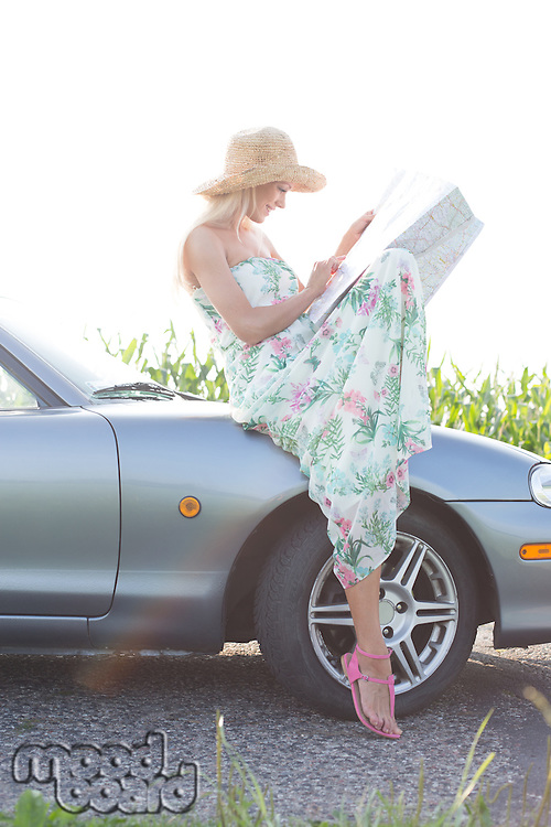 Woman reading map while sitting on convertible