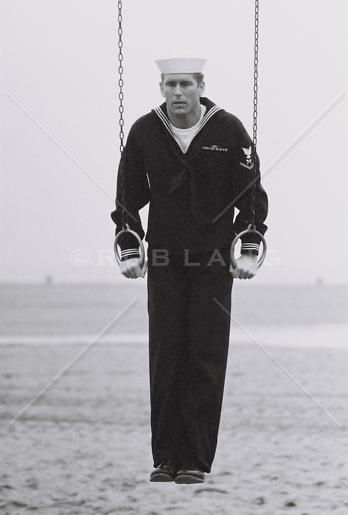 Sailor holding gymnastic rings on the beach