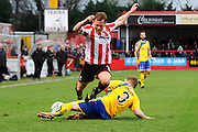 Jack Barthram is tackled during the Vanarama National League match between Cheltenham Town and Altrincham at Whaddon Road, Cheltenham, England on 19 December 2015. Photo by Carl Hewlett.