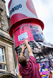 Edinburgh Scotland 7th August 2016 :: Performers from Fringe shows entertain in the High Street to promote their shows.<br /> <br /> A performer placing a poster for his show on a pillar in the High Street<br /> <br /> (c) Andrew Wilson | Edinburgh Elite media