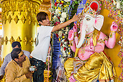 """09 SEPTEMBER 2013 - BANGKOK, THAILAND: Hindus in Bangkok, Thailand, anoint a statue of Ganesha during Ganesha Chaturthi services at Shiva Temple. Ganesha Chaturthi also known as Vinayaka Chaturthi, is the Hindu festival celebrated on the day of the re-birth of Lord Ganesha, the son of Shiva and Parvati. The festival, also known as Ganeshotsav (""""Festival of Ganesha"""") is observed in the Hindu calendar month of Bhaadrapada. The date usually falls between 19 August and 20 September. The festival lasts for 10 days, ending on Anant Chaturdashi. Ganesha is a widely worshipped Hindu deity and is revered by many Thai Buddhists. Ganesha is widely revered as the remover of obstacles, the patron of arts and sciences and the deva of intellect and wisdom.     PHOTO BY JACK KURTZ"""