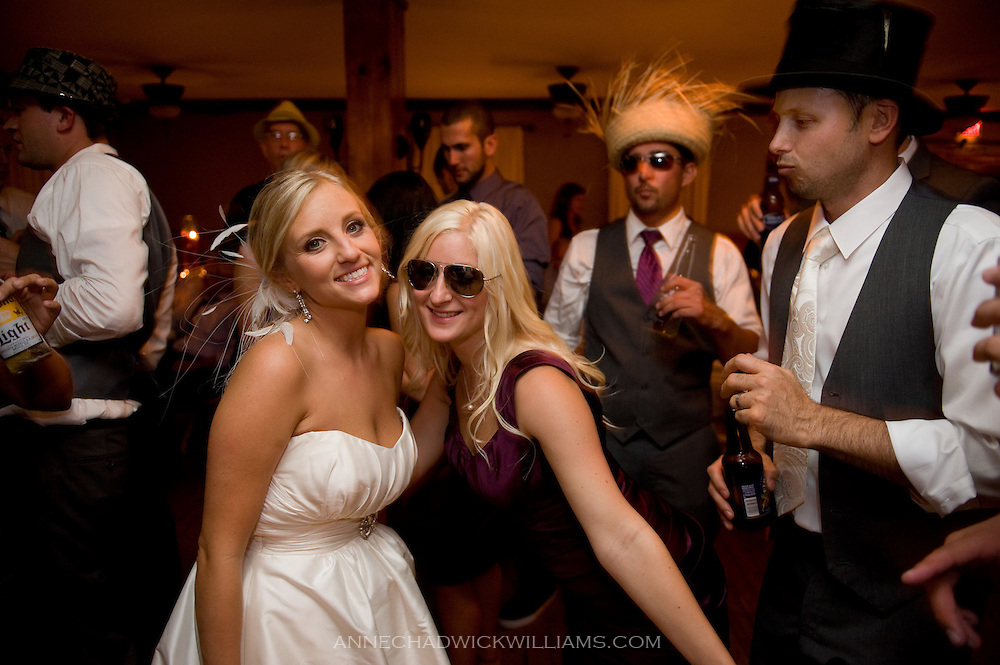 A bride and groom dance with friends at their wedding at Forest House Lodge in Foresthill, CA.