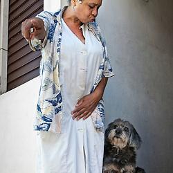 Woman with hair curlers and her dog, Santiago de Cuba, Cuba, Caribbean.