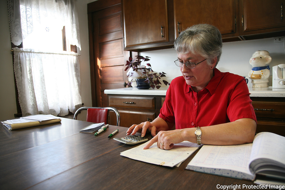 Karen Johnson prepares the family taxes in the kitchen of her farm home near Avoca, Iowa.  <br /> <br /> Karen, along with her husband Bill, have authored two books giving firsthand advice on how to look, listen, laugh and survive in rural America. Photo by David Peterson