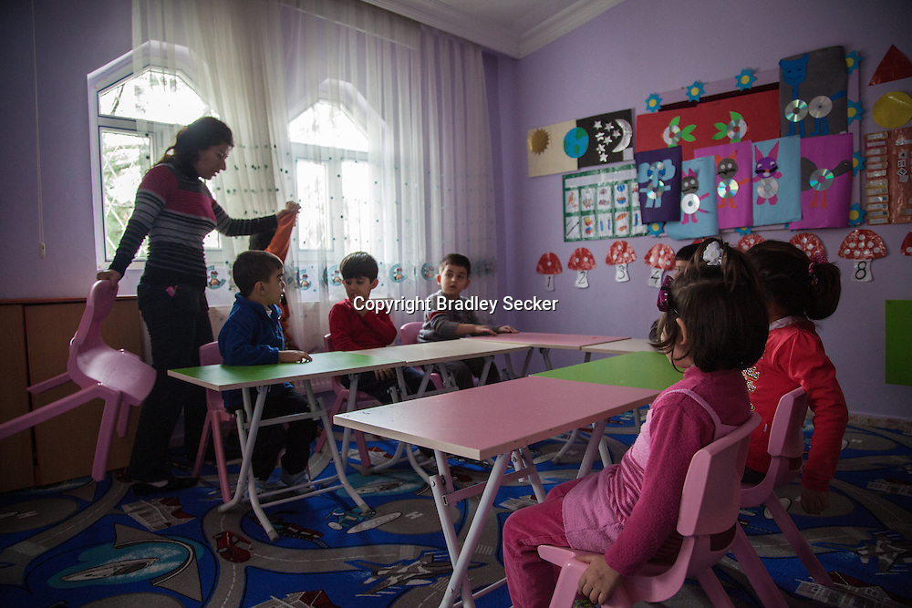 DIYARBAKIR, TURKEY. FEBRUARY 22, 2013 Teacher Valide, left, begins her class for young Kurdish children in Diyarbakir. The creche only teaches in Kurdish, something which was banned until recently in Turkey.