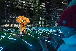 © Licensed to London News Pictures. 18/01/2020. LONDON, UK. A visitor takes a photo on her phone of Squiggle by Angus Muir Design at the sixth Winter Lights festival in Canary Wharf.  25 light art and interactive installations by international artists are on display for the public to enjoy until 25 January 2020.  Photo credit: Stephen Chung/LNP
