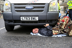 © Licensed to London News Pictures. 07/10/2019. London, UK. An environmental and climate change activist from the Extinction Rebellion group chained and glued under a van outside Department for Business, Energy and Industrial Strategy in Westminster as the protesters are calling for the UK Government to take responsibility and enact immediate, profound and sweeping changes to address the crisis on climate and ecological changes. Photo credit: Dinendra Haria/LNP
