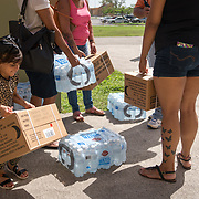 OCTOBER 20 - PONCE, PUERTO RICO - <br /> Residents of Ponce, carry away donated water and MRE's in a distribution center in a sports arena in the Southern town of Ponce, the 2nd largest city in Puerto Rico. <br /> (Photo by Angel Valentin/Freelance)
