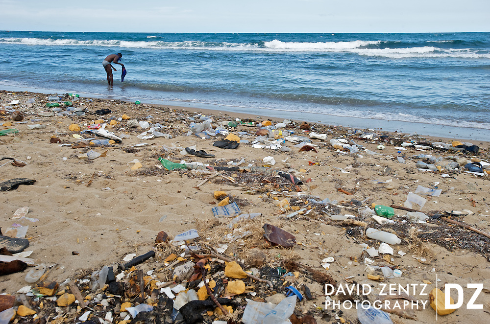 A man rinses his clothes off in the Atlantic Ocean on a trash-strewn beach on the north end of Cap Haitien, Haiti on July, 26, 2008. Litter is a problem throughout the island nation, particularly in the urban centers.