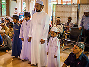 25 JUNE 2017 - BANGKOK, THAILAND: A family prays together in Ton Son Mosque before Eid al-Fitr services. Eid al-Fitr is also called Feast of Breaking the Fast, the Sugar Feast, Bayram (Bajram), the Sweet Festival or Hari Raya Puasa and the Lesser Eid. It is an important Muslim religious holiday that marks the end of Ramadan, the Islamic holy month of fasting. Muslims are not allowed to fast on Eid. The holiday celebrates the conclusion of the 29 or 30 days of dawn-to-sunset fasting Muslims do during the month of Ramadan. Islam is the second largest religion in Thailand. Government sources say about 5% of Thais are Muslim, many in the Muslim community say the number is closer to 10%.    PHOTO BY JACK KURTZ