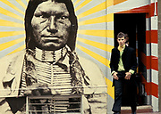 Two teenagers in suits coming out of a building with a Red Indian mural on the wall, UK 1960's