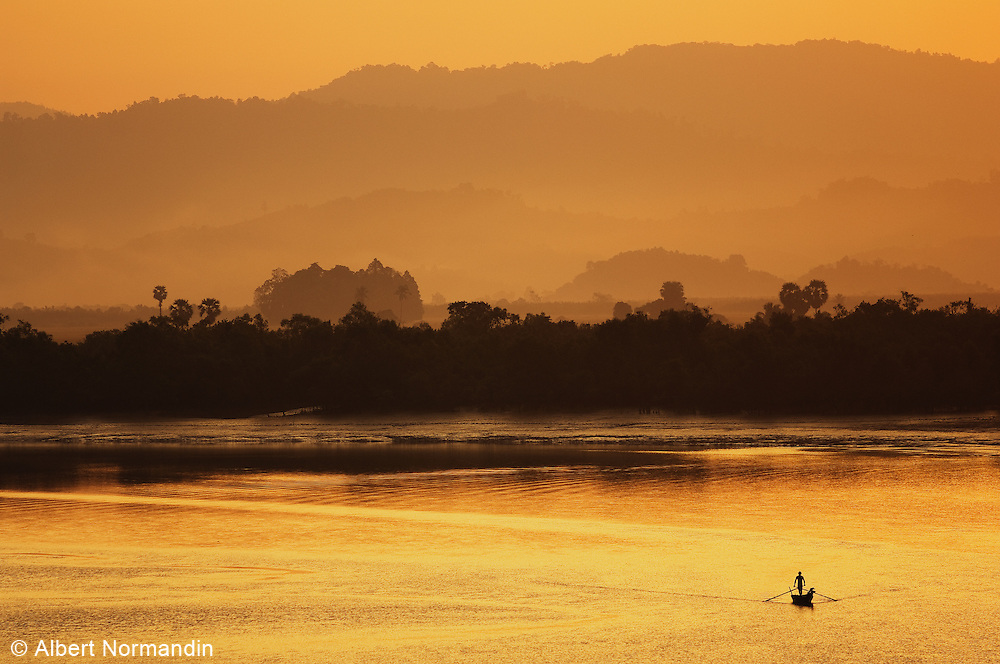Orange sunrise over The Great Tenasserim river and mountains, man rowing boat