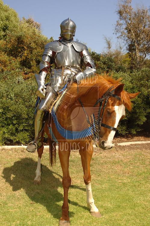 15th century knight in shining armour on horseback
