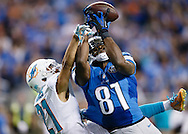 Detroit Lions wide receiver Calvin Johnson (81) makes a catch over Miami Dolphins cornerback Brent Grimes (21) during an NFL football game at Ford Field in Detroit, Sunday, Nov. 9, 2014. (AP Photo/Rick Osentoski)