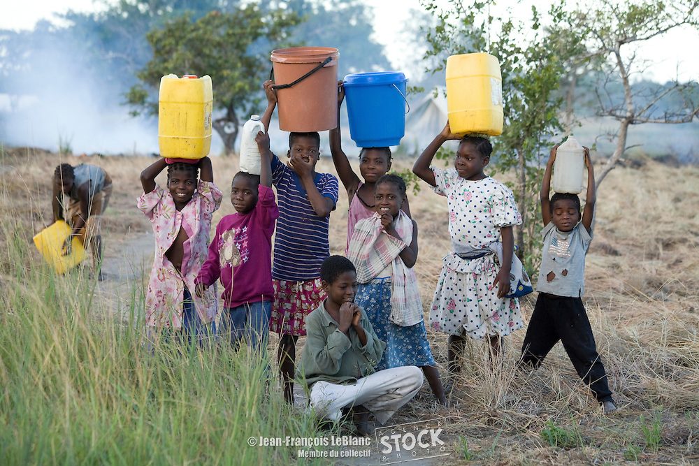Des enfants transportent des sceaux et des bidons d'eau potable dans un camp de réfugiés près de Govuro au Mozambique, suite à des inondations survenues dans la région. 2008.